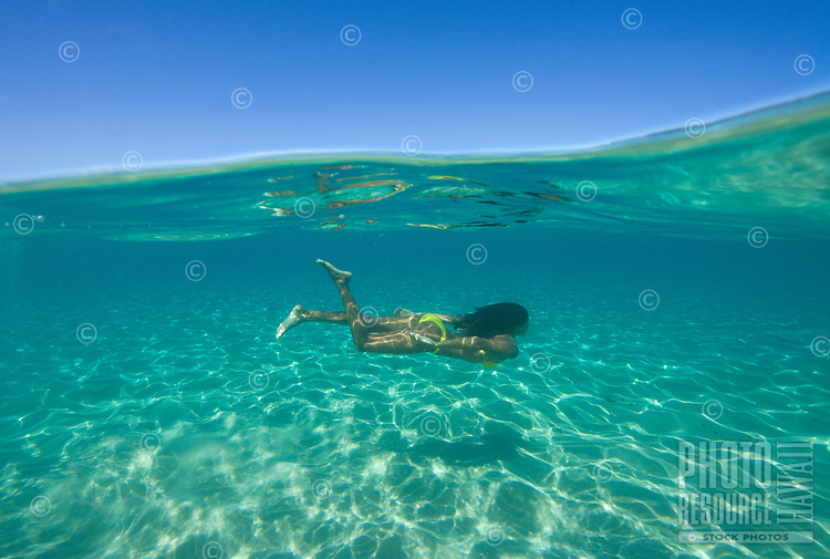 Above and below view of a woman swimming underwater in Ka'anapali, Maui.