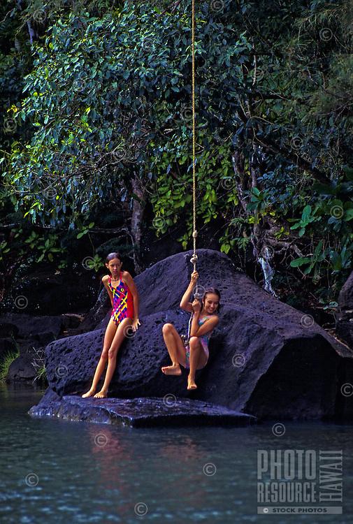 Girls jumping from rope swing into pool. Kalihiwai River, North shore, Kauai