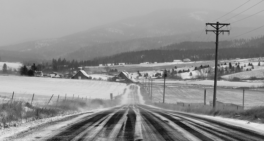 High winds blow snow across the roadway on a highway in the Palouse region of Eastern Washington State.