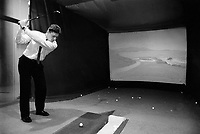 Switzerland. Geneva. A businessman, dressed with a suit and tie, practices indoor golf. He hits the ball into a large movie screen. © 1988 Didier Ruef