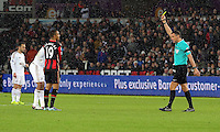 Junior Stanislas of Bournemouth is shown a yellow card by match referee Andrew Marriner during the Barclays Premier League match between Swansea City and Bournemouth at the Liberty Stadium, Swansea on November 21 2015