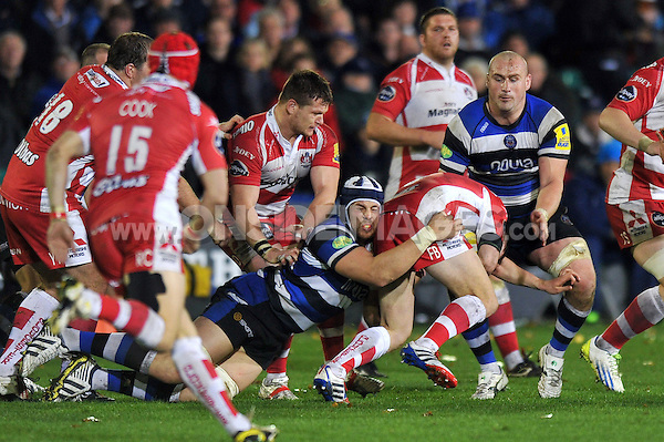 Freddie Burns is double-tackled by Dave Attwood and Carl Fearns. Aviva Premiership match, between Bath Rugby and Gloucester Rugby on October 25, 2013 at the Recreation Ground in Bath, England. Photo by: Patrick Khachfe / Onside Images