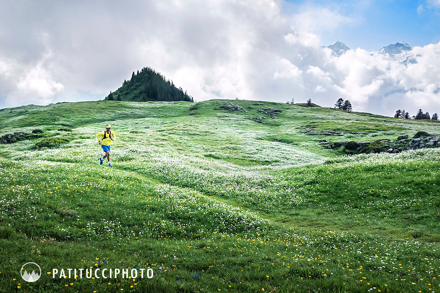 Trail runner passing through a green, flower filled meadow above Interlaken with the Jungfrau starting to appear in the clouds.