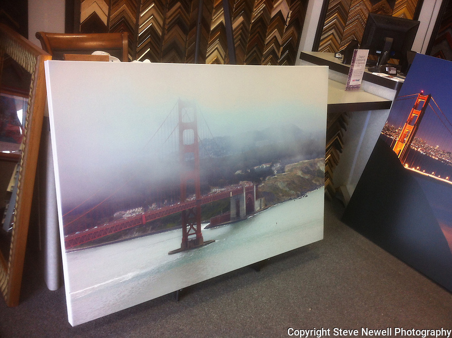 """Park and Ride""  Golden Gate Bridge and The Presidio Park, San Francisco.  A stretched canvas print at the frame shop leaning against the counter. It is a 40x60"" museum wrap. I specialize in Large Oversize Fine Art Landscapes. This close up of the bridge with the Presidio behind it was taken from the Marin side of the Golden Gate Bridge.  I was lucky to have the clouds blowing in off the Pacific Ocean and changing every ten minutes."