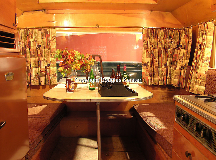 The camper, which was manufactured by the Wolverine Camper Company in Glaswin, Michigan, had the feel of a cozy cabin, thanks to its honey-toned wood interior. Although somewhat spartan by today's standards, the Wolverine was equipped with the basic necessities of a stove, refrigerator, chemical toilet, bed, and table. Amongst the beverages on the table is a bottle of Courvoisier Cognac, a libation that Steinbeck had a predilection for and celebrated in a number of his writings. The typewriter, while not the one that was used to write his travel journals, is similar to the real one, a Swiss-made Hermes Baby, which resides at the Center for Steinbeck Studies at San Jose State University.