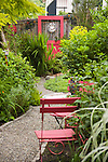 detail of a gravel garden path leading between lush beds, past red painted metal chairs, and towards a red painted door used as funky garden art at the far end in this residential bakyard garden that has removed its lawn in place of lush beds of flowers and foliage