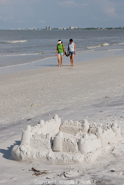 Two beach lovers walk on the white sands of fort Myers Beach.