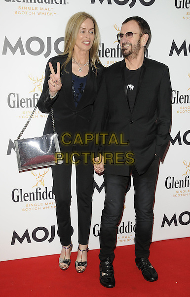 BARBARA BACH & RINGO STARR.The Glenfiddich MOJO Honours List award ceremony, the Brewery, Chiswell St., London, England..July 21st, 2011.full length couple beard facial hair sunglasses shades jeans denim black jacket top hand v peace sign silver bag purse .CAP/CAN.©Can Nguyen/Capital Pictures.
