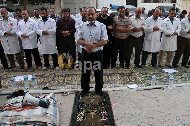 Palestinian employees of the former government in Gaza Strip pray during a protest against not receiving their salaries, in front of the home of Minister of Labor Mamoun Abu Shahla, in Gaza City on July 03, 2014. Many issues involving the Strip, such as the fate of former employees of the Hamas government, have yet to be addressed by the new unity government. Photo by Mohammed Asad