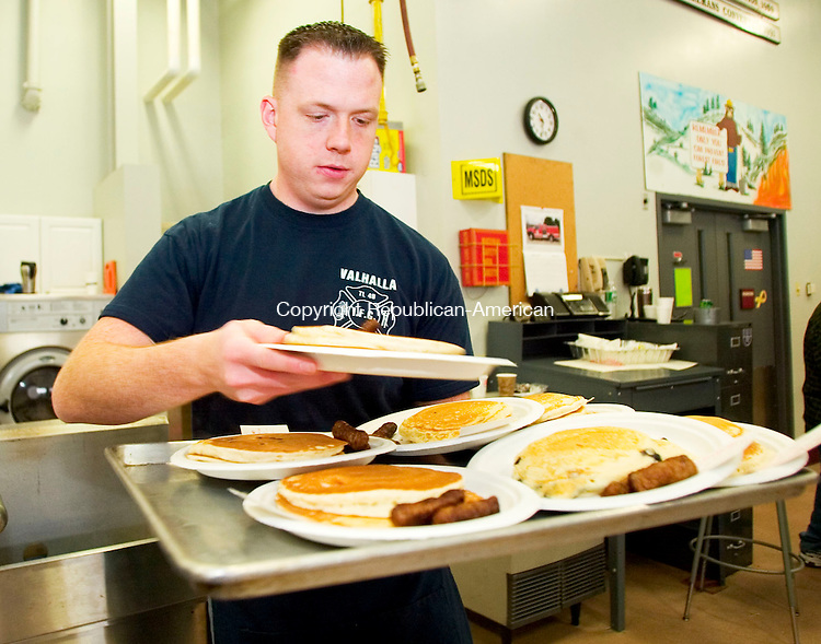 OXFORD, CT- 22 MARCH 07- 032507JT06- <br /> Brian Nethercott, a member of the Oxford Center Volunteer Fire Company No. 1, prepares of a tray of orders during a benefit pancake breakfast on Sunday. The breakfast will benefit a member's family in need of a heart transplant.<br /> Josalee Thrift Republican-American
