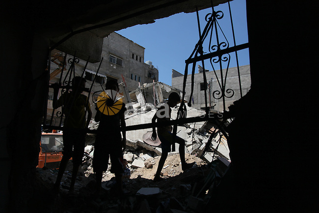 """Palestinian boys search in the debris of their family's house after it was hit by an Israeli military strike in Gaza city on August 10, 2014. A senior Hamas official said there was a """"weak"""" possibility that Gaza truce talks would succeed and that Palestinian negotiators could leave Cairo after a meeting with Egyptian mediators. Photo by Ezz Zanoun"""
