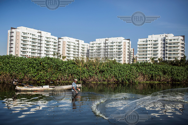 Laiston Luiz fishes in Lagoa da Jacarepagua, which sits in the shadows of newly built luxury condominium complexes. <br /> Two decades of development has destroyed much of the area's natural habitat area and newly built luxury condominiums release raw sewage into the once-pristine lagoons and their connecting canals.