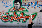 "A Palestinian woman walks by a graffiti of Iehia Aiash known as ""the engineer""  a Hamas military leader killed by Israel, and a graffiti of an Israeli exploded bus, (Aiash was responsible for many suicide operations targeting Israeli busses)  outside the Islamic university in Gaza Strip. Photo by Quique Kierszenbaum"