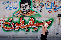 """A Palestinian woman walks by a graffiti of Iehia Aiash known as """"the engineer""""  a Hamas military leader killed by Israel, and a graffiti of an Israeli exploded bus, (Aiash was responsible for many suicide operations targeting Israeli busses)  outside the Islamic university in Gaza Strip. Photo by Quique Kierszenbaum"""