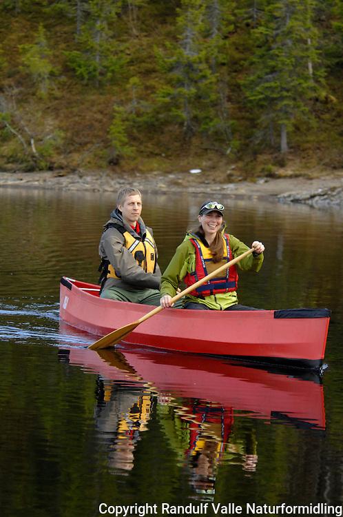 Kvinne og mann padler kano på stille vann ---- Woman and man kanoeing
