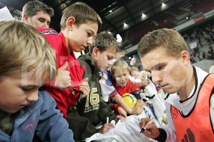 Fussball Deutsche Nationalmannschaft Training in Koeln Lukas Podolski gibt kleinen Fans Autogramm