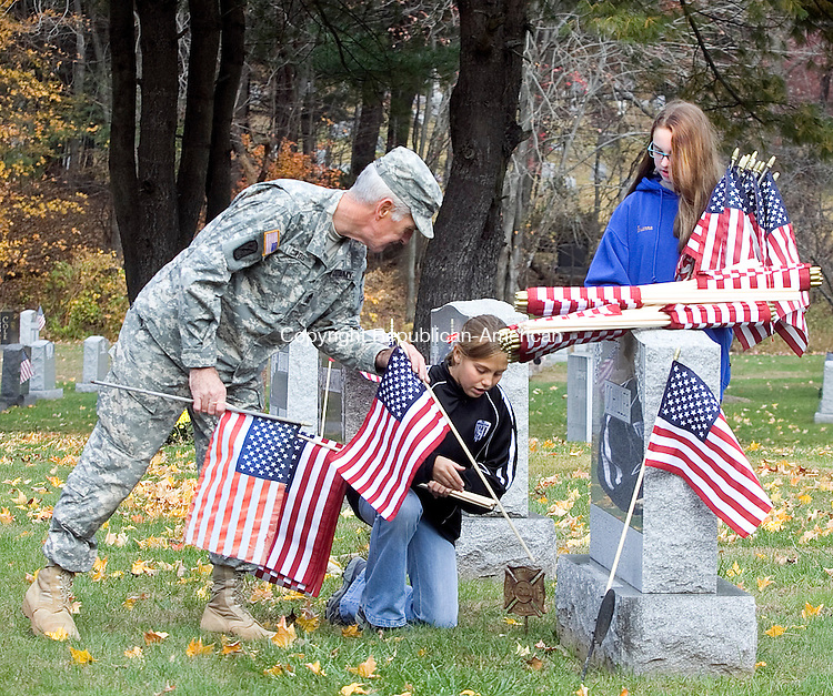 NAUGATUCK CT.-30 OCTOBER 2010 102910DA02- Iraq War Veteran, Bryan Curtis helps Madison Jense place a flag next to a headstone to recognize and honor a military veteran who has passed on as Brianna Durante holds remaining flags to be placed at St. James Cemetery in Naugatuck on Friday. The girls are members of student council and were on hand to help the Veteran Council place eighteen hundred flags at the cemetery along with other 7th and 8th-grade students of City Hill Middle School in Naugatuck.<br /> Darlene Douty Republican-American