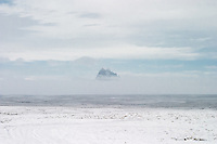 Shiprock Pinnacle or Peak, also known as Tse Bit' a'i in Navajo on the Navajo Nation in New Mexico barely visible through snow and clouds.