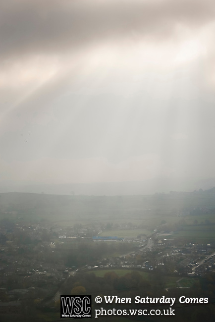 The sun struggling to break through clouds above the town of Stocksbridge. Stocksbridge Park Steels v Pickering Town, Evo-Stik East Division, 17th November 2018. Stocksbridge Park Steels were born from the works team of the local British Steel plant that dominates the town north of Sheffield.<br /> Having missed out on promotion via the play offs in the previous season, Stocksbridge were hovering above the relegation zone in Northern Premier League Division One East, as they lost 0-2 to Pickering Town. Stocksbridge finished the season in 13th place.