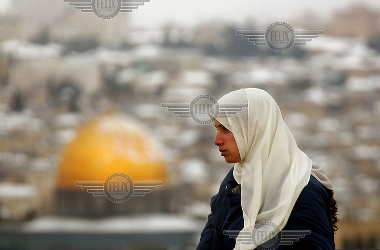 A Palestinian woman from East Jerusalem wearing a traditional headscarf, or hijab pauses with the Old City and the Dome of the Rock Mosque in the background after a heavy rare snow storm.