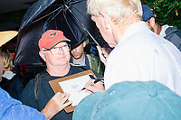 Surrounded by media, former Mass. governor Bill Weld, a Republican presidential candidate, signs an autograph on a rainy day at the Iowa State Fair in Des, Moines, Iowa, on Sun., Aug. 11, 2019.