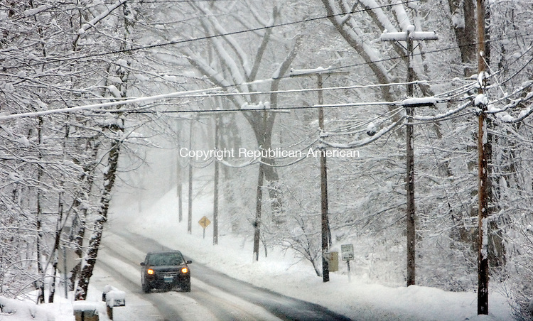 MIDDLEBURY, CT. 08 March 2013-030813SV07-Snow hangs from the trees and wires as cars pass along Tucker Hill Road during the recent snowstorm in Middlebury Friday..Steven Valenti Republican-American