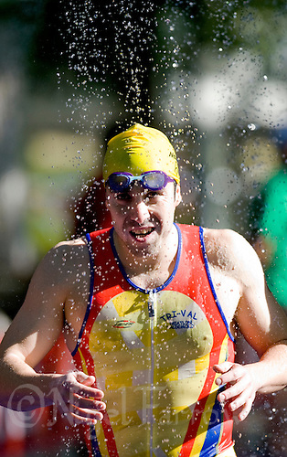 30 MAY 2009 - MADRID,ESP - A competitor runs through the showers at the swimexit - Spanish Triathlon Championships .(PHOTO (C) NIGEL FARROW)