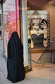 A Muslim woman wearing a niqab waits outside an Accessorize store in Oxford Street.