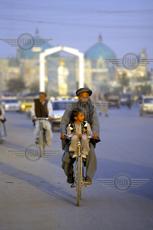 A father and his son ride a bike a long a road in Mazra-i-Sharif, Afghanistan.