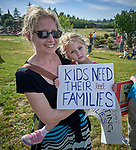 A mother holds a girl holding a sign at a rally outside a federal detention center in Sheridan, Oregon. Participants protested the Trump administration's policy of separating parents from their children at the U.S.-Mexico border.
