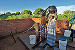 Florence Shawa gets assistance as she begins to carry water home from a well in her village of Thundira, in northern Malawi.