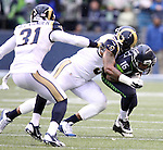Seattle Seahawks wide receiver Tyler Lockett (16)  is hit by St. Louis Rams defensive tackle Eugene Sims (97) after catching a pass at CenturyLink Field in Seattle, Washington on December 27, 2015.  The Rams beat the Seahawks 23-17.      ©2015. Jim Bryant Photo. All Rights Reserved