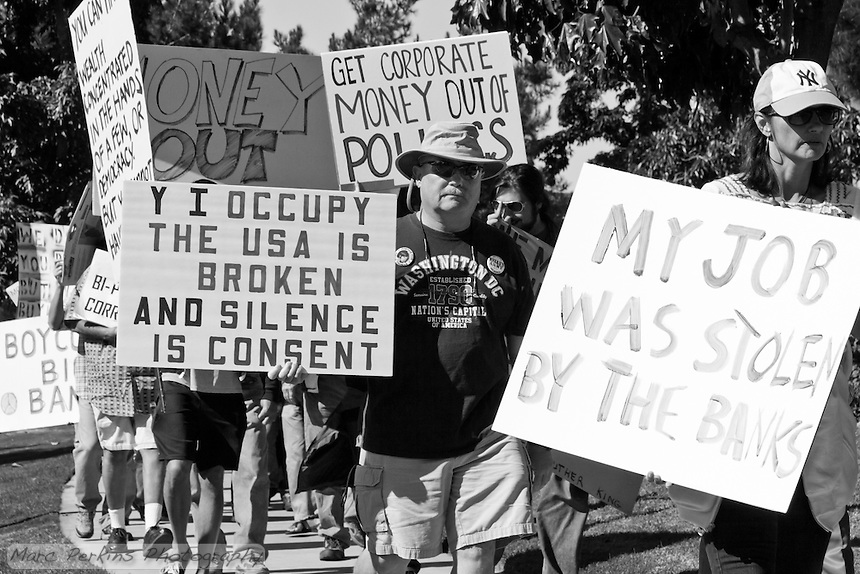 """A man marches in the Saturday November 5 Occupy Orange County, Irvine march looking into the camera holding a sign saying """"Why I occupy: The USA is broken and silence is consent""""."""