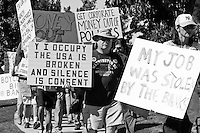 "A man marches in the Saturday November 5 Occupy Orange County, Irvine march looking into the camera holding a sign saying ""Why I occupy: The USA is broken and silence is consent""."