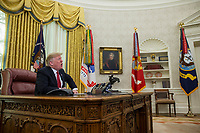 United States President Donald J. Trump makes a video call to service members from the Army, Marine Corps, Navy, Air Force, and Coast guard stationed worldwide in the Oval Office at the White House in Washington, D.C.,  U.S., on December 25, 2018. Photo Credit: Zach Gibson/CNP/AdMedia