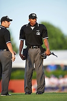 Umpires Grant Conrad and Edwin Moscoso discuss a call during a game between the Hagerstown Suns and Lexington Legends on May 22, 2015 at Whitaker Bank Ballpark in Lexington, Kentucky.  Lexington defeated Hagerstown 5-1.  (Mike Janes/Four Seam Images)