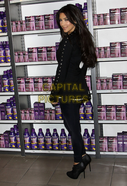 "KIM KARDASHIAN .At a photocall to introduce ""Quicktrim"" held At GNC Beverly Center, Los Angeles, California, USA,.15th October 2009..full length black jacket leggings ankle boots heels ribbon woven silk satin white top looking over shoulder back rear behind studs studded .CAP/ADM/KB.©Kevan Brooks/Admedia/Capital Pictures"