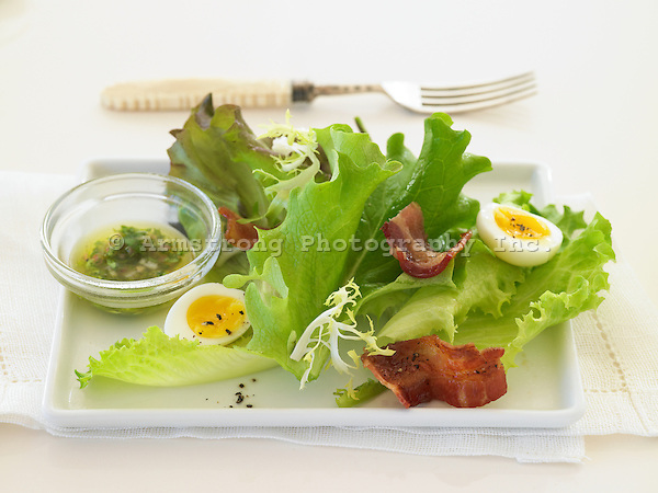 Mixed greens salad with bacon and hard boiled eggs. Dressing on the side