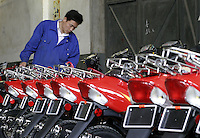 A worker inspects just finished LPG scooters at the Shanghai Forever Bicycle Factory in Shanghai, China. With the worsening of the city's air pollution due to increased vehicle traffic, the city has banned the sales of gasoline powered scooters in favor of ones that run on cleaner LPG..21-APR-04
