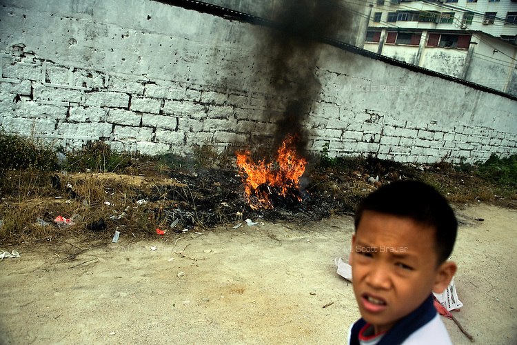 A young boy plays with fireworks near a garbage fire in central Sanya, Hainan, China.