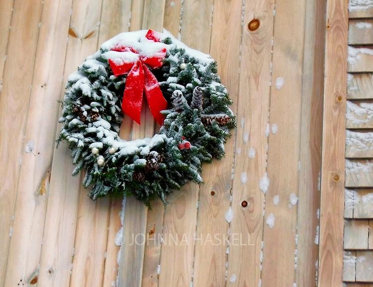 Handmade balsam wreath hangs in fresh snow storm.
