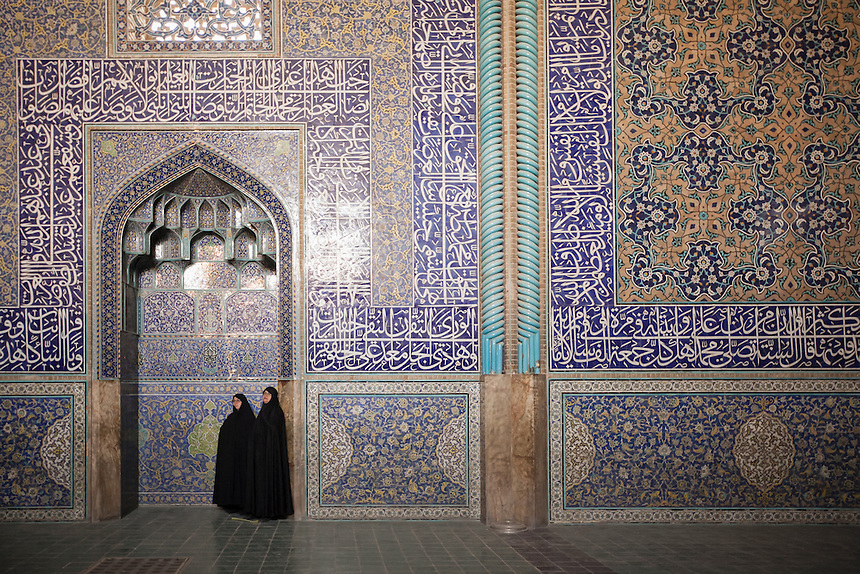 Two Iranian visitors enjoy the marvel of the interior of Sheikh Lotfollah Mosque. Sheikh Lotfollah Mosque is one of the architectural masterpieces of Safavid Iranian architecture, standing on the eastern side of Imam Square (Naqsh-E Jahan), Isfahan, Iran..Construction of the mosque started in 1603 and was finished in 1618. It was built by the chief architect Shaykh Bahai, during the reigh of Shah Abbas I of the Safavid dynasty..It is registered, along with the Imam Square, as a UNESCO World Heritage Site.