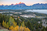 Grand Teton National Park, WY: Sunrise light on the Teton Range with fog in the Snake River Valley in fall