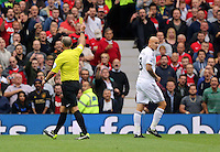Pictured: Jonjo Shelvey (R) of Swansea sees a yellow card by match referee Mike Dean. Saturday 16 August 2014<br />