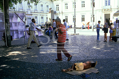 Salvador, Bahia State, Brazil; very young homeless street kid sleeping on a cardboard box in a public park.