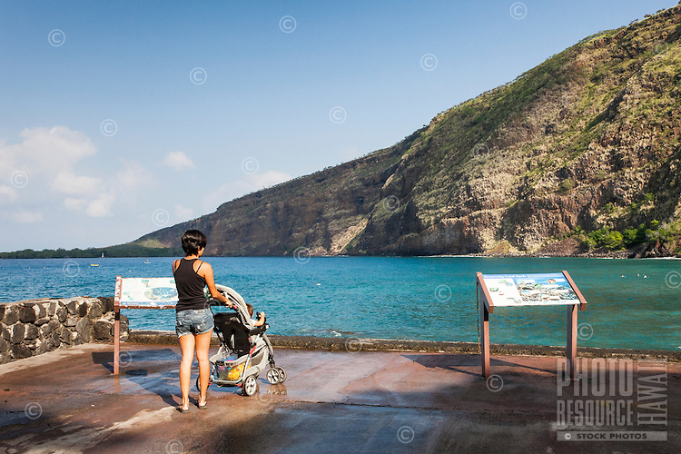 A young woman with a baby in a stroller at Kealakekua Bay, Big Island.