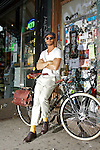 A well dressed man leans against his bicycle in Williamsburg, NY.  He wears yellow socks, sunglasses, and a plain white t-shirt.  The bicycle has large white walled tires and a leather saddle bag hanging off the back.