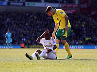 Pictured L-R: Dwight Tiendalli of Swansea on the ground after being brought down by Robert Snodgrass (not pictured) of Norwich while Bradley Johnson is asking him to get up. Saturday 06 April 2013<br />