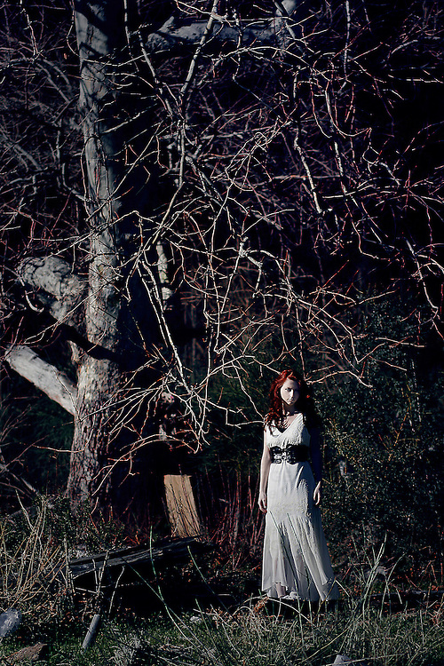 A girl in a white dress standing under a large tree.