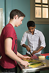 Education high school classroom scenes teenage boys cutting vegetables in elective cooking class